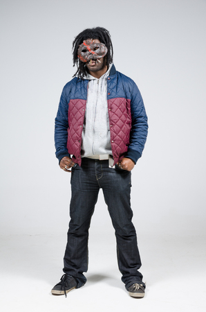 A scary african american male wearing a scary mask photographed against a white infinity curve background in a studio. A horror movie urban street character.
