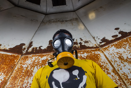 A scary man with reflection eyes in an industrial setting wearing a horror gas mask staring and intimidating. A horror movie character. Stock Photo