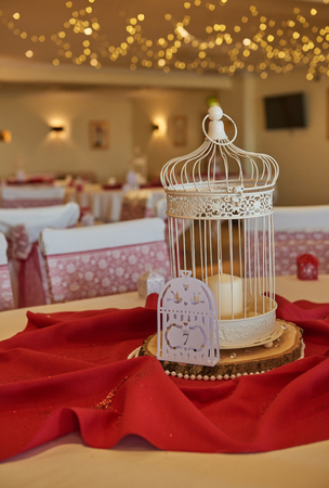 gorgeous intricate wedding details and table setting in warm red and yellow environment with fairy lights out of focus in the background.