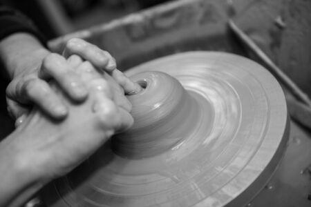 Manos trabajando en una rueda de cerámica de hilado, haciendo alfarería de barro de arcilla. cerca de la fotografía con una profundidad de campo.