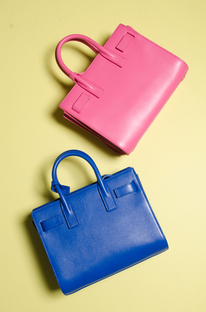 A leather designer handbag, floating against a background, shot in a studio with sharp light and vivid blue and pink colours