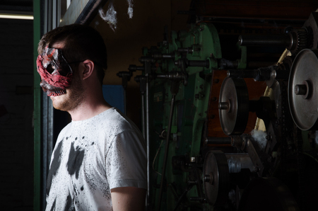 intimidating: A scary man in an industrial setting wearing a horror mask staring and intimidating. A horror movie character.