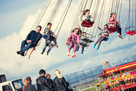 chain swing ride: london, england, 05052017 Children swinging in the air on a chair swing ride carousel, swing carousel. Children having fun on a fairground ride.