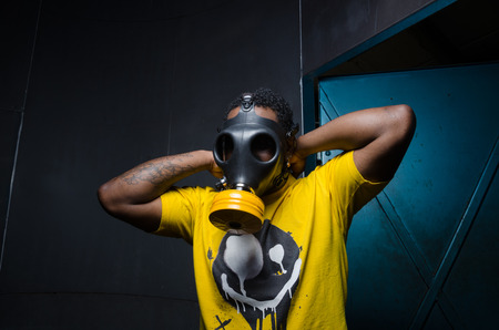 intimidating: A scary man with reflection eyes in an industrial setting wearing a horror gas mask staring and intimidating. A horror movie character. Stock Photo