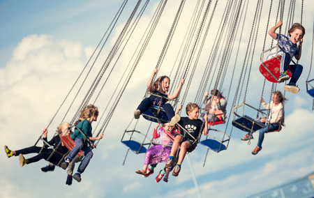 london, england, 05052017 Children swinging in the air on a chair swing ride carousel, swing carousel. Children having fun on a fairground ride.