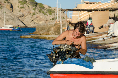 ibiza, spain, 02022016, A Spanish hippy man in ibiza, fixing his engine on his fishing boat. the man is in the water, preparing the boat for a fishing trip.