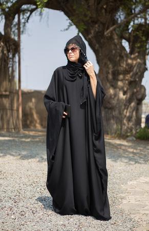 Una bella donna occidentale in posa al sole con il suo dispositivo tablet cellulare, indossando un tradizionale abito burka hijab arabo. donna mediorientale libertà e diritti. Moda araba.