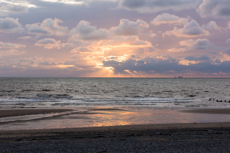 A pink and blue creamy cloudy sunset, with sun rays breaking through the clouds. A relaxed quiet sunset evening on the coast.