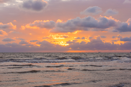 sun energy: A pink, blue and purple creamy cloudy sunset, with sun rays breaking through the clouds. A relaxed quiet sunset evening on the coast. Stock Photo