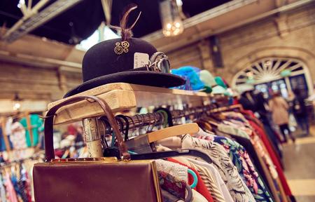 Sombrero de segunda mano del vintage y carril de la ropa que muestra la ropa colorida de la vendimia en suspensiones de capa. Foto de archivo