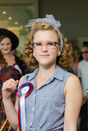 london, England, 05052017, A stylish retro vintage fashionable woman in glasses and a light blue american retro dress blouse in a Best dressed award at a vintage event..