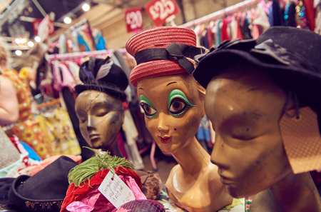 Vintage second hand hats on unusual retro ugly head mannequins, and a clothes rail showing colourful vintage clothes on coat hangers.