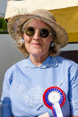 london, England, 05052017, A stylish retro vintage fashionable old woman with blue clothing, retro sun glasses, vintage straw hat, and a rosette, in a Best dressed award at a vintage event..