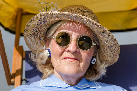 're: london, England, 05052017, A stylish retro vintage fashionable old woman with blue clothing, retro sun glasses, vintage straw hat, and a rosette, in a Best dressed award at a vintage event..