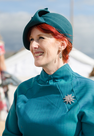 're: london, England, 05052017, A stylish retro vintage fashionable woman with red hair, 1940s blue clothing, and a silver broach in a Best dressed award at a vintage event..