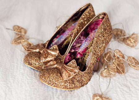 Een bruiden mooie, gouden, glittery, sexy paar individuele stijlvolle trouwschoenen, op een wit romig materiaal oppervlak. Stockfoto