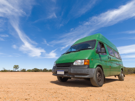 A old green backpackers motorhome camper van, in the Australian outback, with a vivid blue sky and famous red dirt floor. The Australian outback is a great place for travellers. Stock Photo