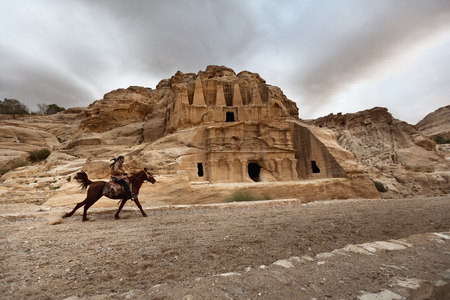 Petra, Jordan, 05052017, A Jordandan male riding horse back in Jordan with a famous petra sculpture in the background. Storm clouds above the monument. Editorial