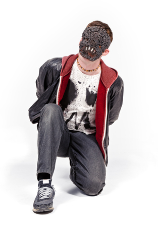 A man wearing a scary mask, photographed against a white infinity curve background in a studio. A horror movie urban street character. Stock Photo