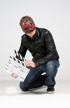 A man wearing a scary mask, holding a blank film clapper board, photographed against a white infinity curve background in a studio. A horror movie urban street character.