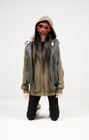 A woman with a red scary horror mask against a white infinity curve background in a studio. A horror movie urban street character.