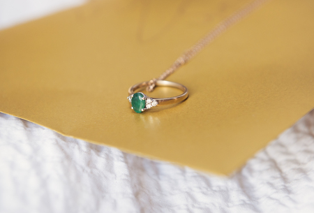 A beautiful expensive green emerald wedding ring with tiny diamonds on a rustic golden bohemian background. Photographed with a shallow depth of field.