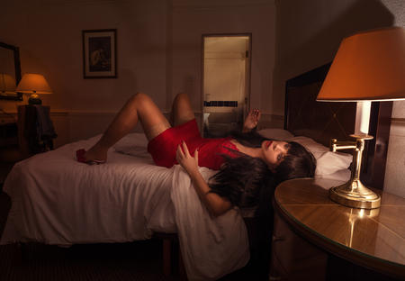 london, england, 05/05/2017, A real life artificial adult entertainment doll dressed in red lingerie, lying stiff on a motel hotel bed. Adult dolls are replacing women in some cultures.