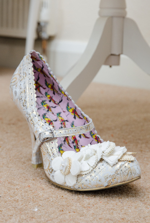 london, england, 0505201, A brides beautiful, white, paisley  glittery, sexy pair of individual stylish wedding shoes, on a white creamy material surface.