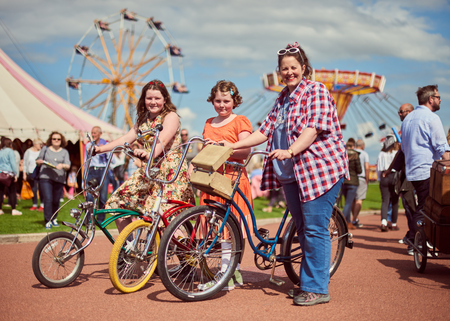 morecambe, England, 05052017, A group of stylish retro vintage  women holding vintage chopper bicycle nikes acting and posing in fancy dress cosplay  at a vintage event at the Midland hotel.