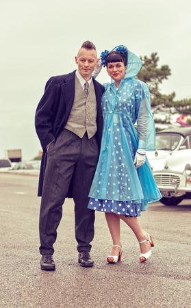 london, england, 05/07/2017 , A retro and vintage dressed man and woman in 1950s clothing, man with a quiff and woman in a blue rain macintosh, at a vintage retro nostalgic event.