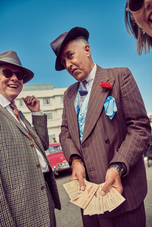 london, england, 05/05/2017, A main in 1920s fancy dress as a mobster mafia con artists seller of fake and stolen goods on his wrist. Handsome and untrustworthy street trader. Fashionable pin sniper suit.