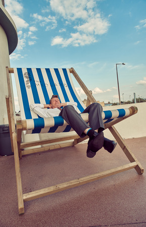 london, England, 05052017, A stylish retro vintage fashionable man sat relaxing with arms on head, on a giant retro seaside deckchair. Giant deckchair. Best dressed award.  Editorial
