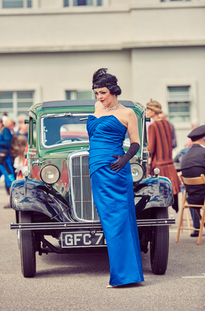 london, england, 02/05/217, A gatsby girl in 1920s Art deco style party girl flapper clothing, and feather head wear, black gloves and blue dress,  posing by a  vintage retro car.  Editorial