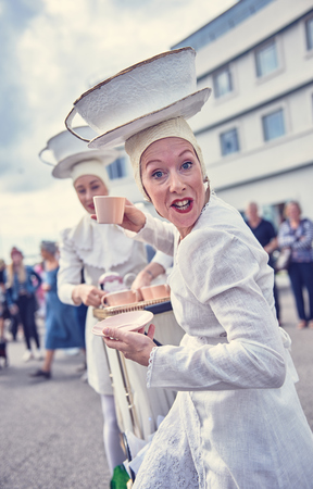 london, England, 05052017, A woman in a retro vintage fantasy, white tea lady costume, with an english cup of tea and a giant cup of tea hat. Best dressed award at a vintage event..  Editorial