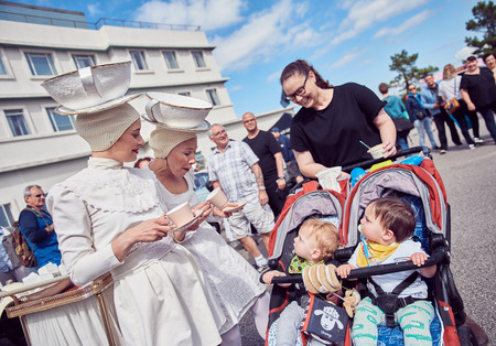 london, England, 05/05/2017, A pair of woman in a retro vintage white fantasy costume talking to children, a tea lady costume with an english cup of tea and a giant cup of tea hat. Best dressed award at a vintage event..