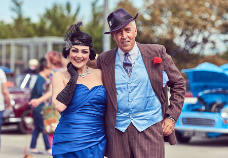 london, england, 05/05/2017, A main in 1920s fancy dress as a mobster mafia con artist, with a Gatsby girl. Handsome and untrustworthy street trader. Fashionable pin stripe suit.