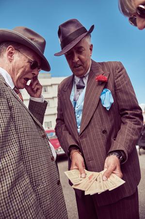 런던, 영국, 05052017, 마술사 마피아 콘 아티스트 그의 손목에 가짜 및 도난 된 상품 판매자의 1920 년대 멋진 드레스의 메인. 잘 생기고 신뢰할 수없는