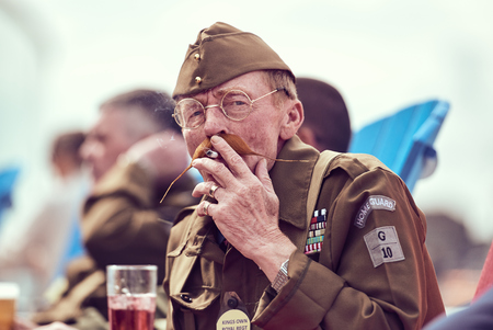 london, England, 05052017, A stylish retro vintage fashionable man dressed in war time world war 2 home guard uniform and long hipster moustache smoking. army uniform. Best dressed award Editorial