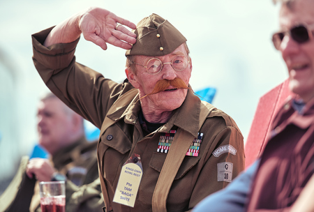 london, England, 05052017, A stylish retro vintage fashionable man dressed in war time world war 2 home guard uniform and long hipster moustache, saluting. army uniform. Best dressed award Editorial