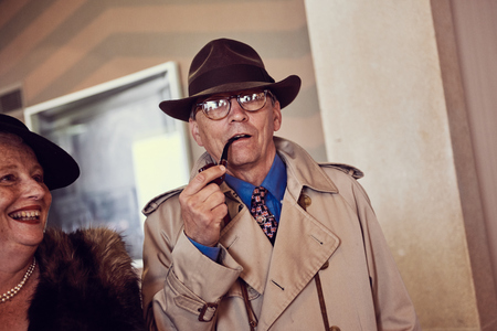 london, England, 05052017, A stylish retro vintage fashionable man in a trench coat macintosh, hat and glasses smoking a pipe. Old american film noir detective inspector style clothing. Best dressed award