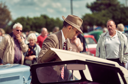 london, England, 05052017, A stylish retro vintage fashionable man in a hat, waist coat and glasses, looking under the bonet of an old car.Old american film noir detective inspector style clothing.