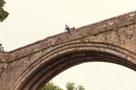 A stunt man dressed up as an elderly vintage gentleman jumping off a high bridge with water below.  Depression and is high in elderly men. Stock Photo