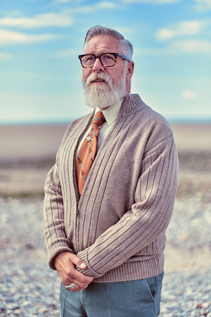 london, England, 05052017, A stylish retro vintage fashionable elder hipster men, with cuban style posing on a warm empty beach.Best dressed award.