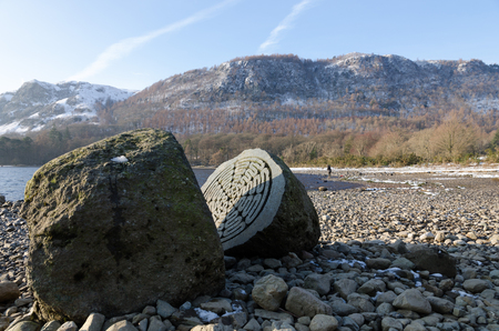 The Lake District, Keswick, England, 01172016, Winter lakeside view with carved stone memorial in the foreground