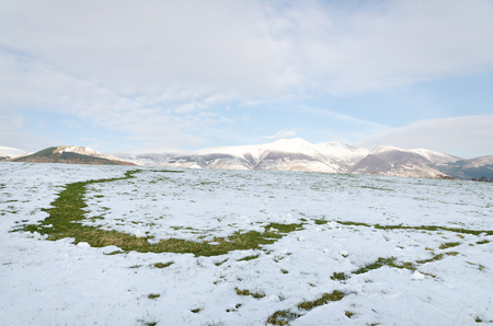 Snowy field with snow covered mountains in the background, The Lake District, Keswick, England Stock Photo