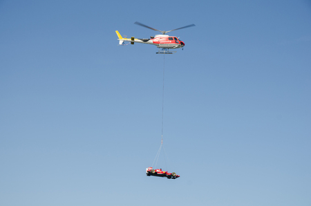 Barcelona, Spain, 05062013, A helicopter flying a Ferrari formula one race car over the city.