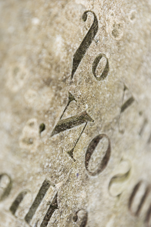 Grungy Abstract Hand carved typeset on an old english gravestone, with a shallow depth of field Stock Photo