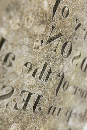 Grungy Abstract Hand carved typeset on an old english gravestone, with a shallow depth of field Foto de archivo
