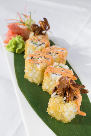 Fresh prawn and fish egg sushi rolls, with wasabi and seafood sauce, served on a green leaf plate.