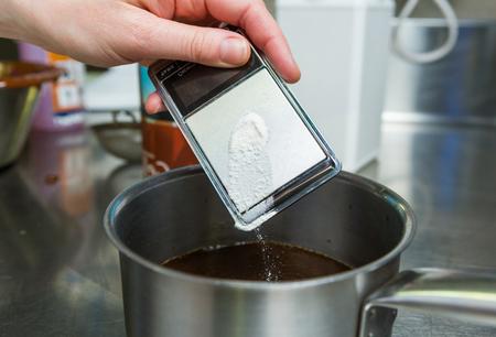 Zout op een digitale meetschaal, in een hete zilveren pan met vloeistof laten vallen.